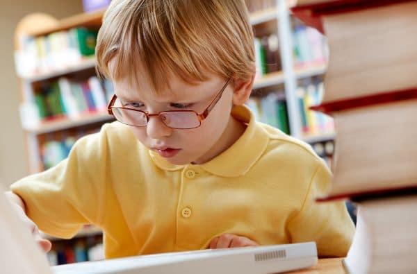 menino com óculos olhando notebook